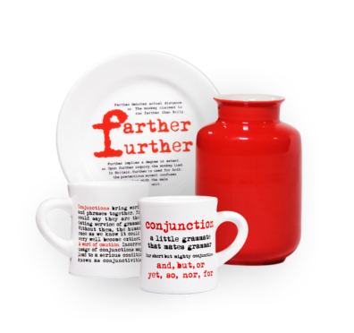 A mug with definition of a Conjunction, a red vase and a plate explaining the difference between farther and further, available at the Signature Theatre Bookstore
